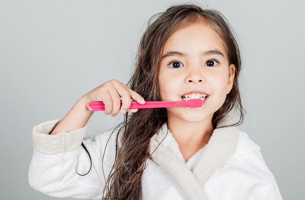 Young girl brushing her teeth after her parents made an appointment at Atlantic Dentistry in Jacksonville, FL